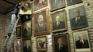 Worker hanging paintings of Lenin
