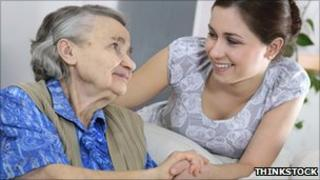 Woman caring for elderly woman (posed by models)