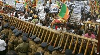 Sri Lankan policemen try to support a barricade during a protest outside the British embassy in Colombo on 3 December 2010