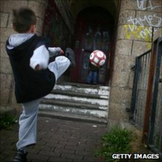 Two young boys play football in a rundown street in Glasgow