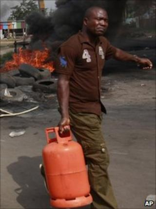 Man carrying bottle of cooking gas