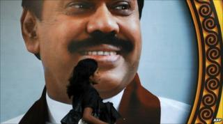 A pedestrian walks past a giant billboard of President Mahinda Rajapaksa on Galle Face promenade in Colombo
