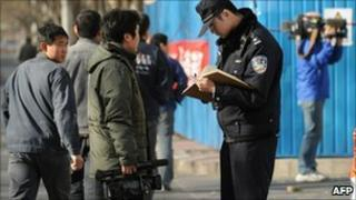 Policeman checks identity papers of journalist in front of Liu Xiaobo's apartment in Beijing - 10 December 2010