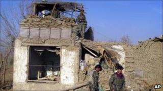 Afghan soldiers at damaged military checkpoint after a suicide attack in Kunduz, 11 December 2012