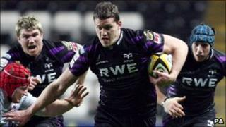 Ospreys' Ian Evans hands off Edinburgh's Kyle Traynor during a recent match at the Liberty Stadium