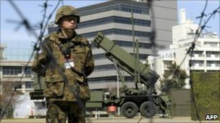 A Japanese soldier stands guard next to an interceptor missile launcher at the Defense Ministry headquarters in Tokyo