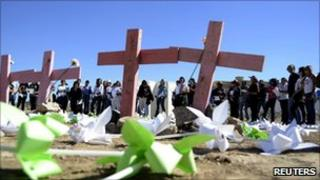 People stand near wooden crosses in a field near Ciudad Juarez where the bodies of eight murdered women were found in November 2010