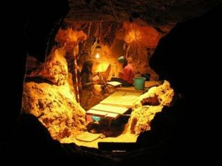 Archaeologists excavate the cave in El Sidron in Asturias, northern Spain