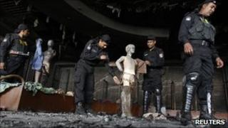 Members of Rapid Action Battalion inspect a burnt garment factory in Ashulia, Bangladesh, on 15 December 2010