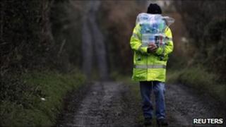 Man walks along country lane carrying bottles of water