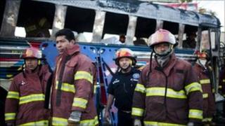 Firefighters beside the scorched bus and the covered body of one of the victims in Guatemala City (3 January 2011)