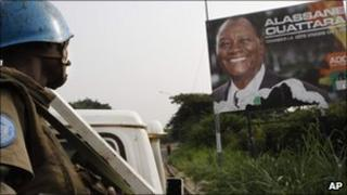 United Nations troops in Abidjan by a billboard of Ivory Coast's internationally recognised elected leader Alassane Ouattara