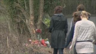 People laying flowers at the crash site