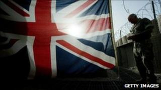 A British soldier stands beside a Union Jack flag at a base in Helmand Province