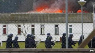 Specialist prison officers in riot gear near a burning building