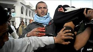 An injured demonstrator is carried away by fellow protesters in the town of Regueb