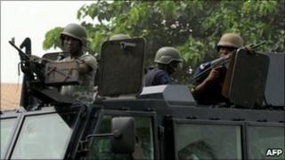 Ivorian gendarmes ride on11 January 2011 in Abidjan's Abobo neighbourhood in the PK18 area