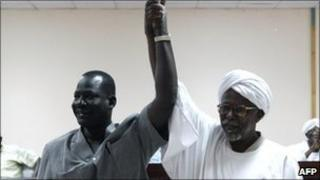 Sudanese Al-Amer Mokhtar Papo (right) a leader of the Misseriya Arab tribe and his counterpart from the Dinka Ngok tribe, Sultan Qoual Dinq Qoual raise their hands after signing a peace agreement in the town of Kadugli north of Abyei on 13 January 2011
