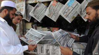 Pakistani men read the headlines at a news stand in Quetta on 4 September 2010