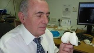 Mike Regan holding a plastic knee joint created from MRI