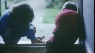 A boy and a girl sitting on a doorstep