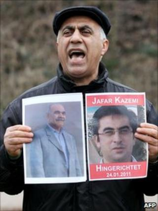 A protester in Hamburg, Germany holds up pictures of Iranian opposition activists Jafar Kazemi and Mohammad Ali Hajaghaei who were hanged in Iran, 24 January 2011