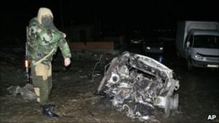 A masked Russian police officer inspects a bomb scene in Khasavyurt, 26 January