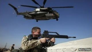 A German soldier keeps watch in Kunduz, Afghanistan, as a helicopter takes off, December 2010