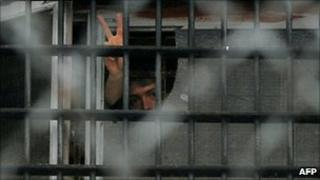 A man gestures from a window at a prison in Minsk, 23/12