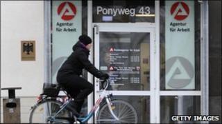 Woman cycles past German job centre