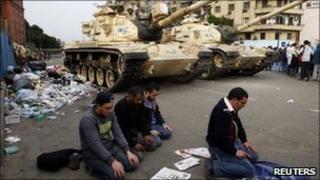 Men pray in front of tanks in Cairo's Tahrir Square - 1 February 2011