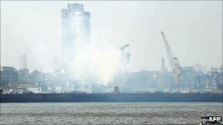 Smoke rises from the stricken ship inside the naval dockyard