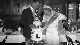 Newlyweds cutting cake with L plate on
