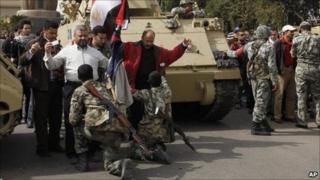 Soldiers search anti-government protesters entering Tahrir Square in Cairo - 4 February 2011