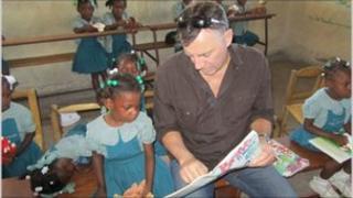 Duncan Bannatyne with children in Cite Soleil, Haiti