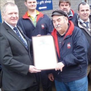 Brian Jeffrey receives an award marking 50 years' service