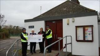 Police community support officers handing the cheque over to parish councillors