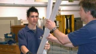 Electrician and his apprentice at work changing a strip light in a factory