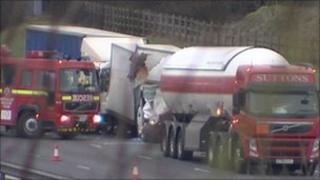Scene of the crash showing a van trapped between gas tanker and another van
