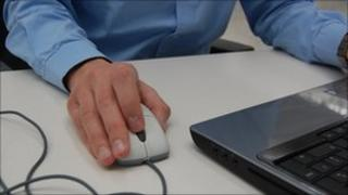 Man holding a mouse attached to a laptop