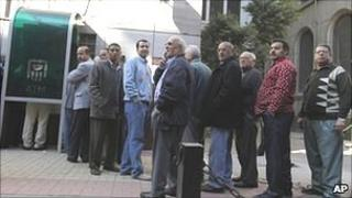 Egyptians queue at an ATM in Cairo prior to the reopening of the banks