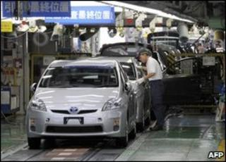 Assembly line worker checks a Prius hybrid car at the Toyota factory