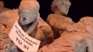 """A banner on a statue in Rome which reads: """"I can't go anywhere, you can"""""""