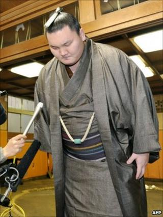 Mongolian-born sumo grand champion, Hakuho bows at the beginning of a press conference at his stable in Tokyo