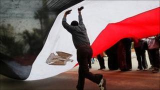 A man runs underneath an Egyptian flag on Tahrir Square (9 Feb 2011)