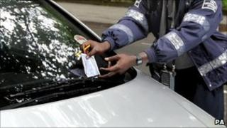 A civil enforcement officer issuing a parking ticket in