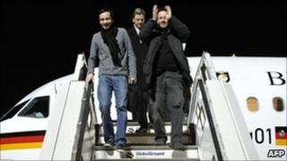 German Foreign Minister Guido Westerwelle (C), Jens Koch (L) and Marcus Hellwig walk off an official German government plane on 20 February 2011