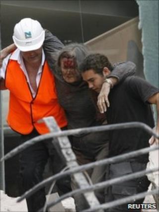 A woman is rescued from inside the Pyne Gould Corporation building after an earthquake in Christchurch