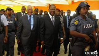 South African President Jacob Zuma (L) walks with Ivory Coast's Alassane Ouattara as they arrive for a meeting in Abidjan, 22 February 2011