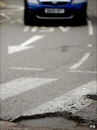 Car approaching pothole